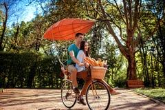 有红色飞船和ba的可爱的年轻夫妇骑马自行车 免版税库存图片