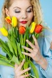 有红色黄色郁金香束的俏丽的妇女 免版税库存图片