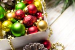 有红色,金黄和绿色圣诞节球的箱子 defocused的背景 免版税库存照片