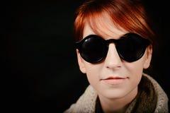 有红色头发和太阳镜的异常的妇女演播室 免版税库存照片