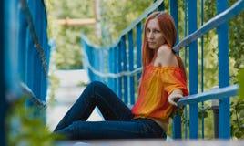 有红色头发和救生服的少妇坐一座小桥梁在夏日 免版税图库摄影