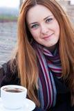 有红色头发和蓝眼睛的喝咖啡的一个美丽的女孩的画象 库存照片