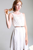 有红色头发和雀斑的美丽的女孩在典雅的白色礼服 免版税库存照片