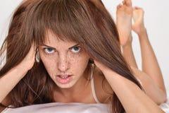 有红色头发和雀斑的美丽的妇女在床上 免版税库存照片