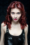 有红色头发和黑上面的美丽的妇女 免版税库存图片
