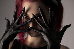 有红色头发和黑油漆的美丽的妇女在手上 免版税库存图片