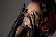 有红色头发和黑油漆的美丽的妇女在手上 免版税库存照片