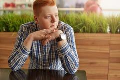 有红色头发的一个可爱的男孩在控制中坐在与结合在一起使手的绿色种植园的舒适咖啡馆的典雅的衬衣穿戴了 库存图片