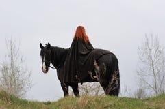 有红色头发的勇敢的妇女在黑白花的马的黑斗篷 免版税库存照片