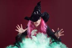 有红色头发的可怕巫婆执行在绿色抽烟的魔术 万圣夜,恐怖题材 免版税库存照片
