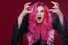 有红色头发的可怕巫婆执行魔术 ?reate某事用手,您的设计的自由空间或作用 免版税库存图片