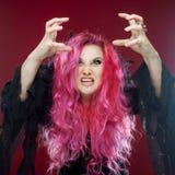 有红色头发的可怕巫婆执行魔术 ?reate某事用手,您的设计的自由空间或作用 免版税库存照片