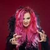 有红色头发的可怕巫婆执行魔术 ?reate某事用手,您的设计的自由空间或作用 库存照片