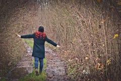 有红色头发的女孩在有很多黄色和灰色分支和叶子的黑外套和帽子走的低谷森林里  免版税库存照片