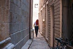 有红色头发的女孩在通过低谷城市微小的浅街道段落的礼服 库存图片