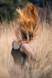 有红色头发的女孩在领域 免版税库存图片