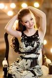 有红色头发的女孩在黑白礼服微笑反对t 库存图片