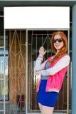 有红色头发的女孩显示一个白色标志 免版税图库摄影