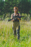有红色头发的女孩从有一杆枪的森林出来在他的手上 免版税图库摄影