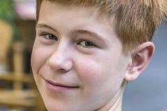 有红色头发的微笑的孩子 免版税库存图片