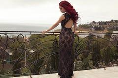 有红色头发的性感的妇女在摆在阳台的豪华礼服 库存图片
