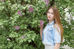 有红色头发的美丽的女孩在有丁香的庭院里 图库摄影