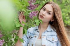 有红色头发的美丽的女孩在有丁香的庭院里 免版税库存图片