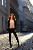 有红色头发的美丽的女孩在街道上 免版税图库摄影