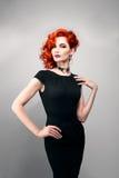 有红色头发的美丽的妇女在一件黑礼服 库存图片