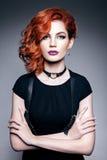 有红色头发的美丽的妇女在一件黑礼服 图库摄影