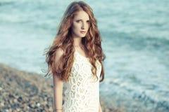 有红色头发的美丽的妇女在海 免版税库存照片
