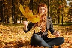 有红色头发的美丽的妇女在秋天公园 免版税图库摄影
