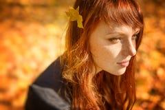 有红色头发的美丽的妇女在秋天公园 图库摄影