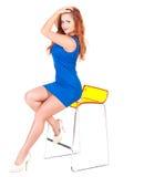 有红色头发的美丽的妇女坐酒吧椅子 库存图片