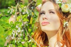 有红色头发的美丽的性感的女孩有在她的头发的花的在开花的苹果树附近站立 免版税图库摄影