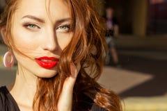 有红色头发的美丽的性感的女孩有有构成的大红色嘴唇的在城市在一个晴朗的夏日 免版税图库摄影