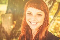 有红色头发的美丽的雀斑妇女在秋天公园 库存照片