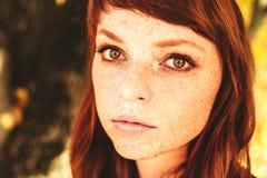 有红色头发的美丽的雀斑妇女在秋天公园 免版税库存图片