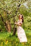 有红色头发的美丽的年轻性感的女孩在开花的树站立在一件桃红色礼服的苹果树附近 免版税图库摄影