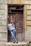 有红色头发的美丽的年轻甜女孩在站立在老城市附近的门的牛仔裤 免版税库存照片