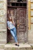 有红色头发的美丽的年轻甜女孩在站立在老城市附近的门的牛仔裤 免版税图库摄影