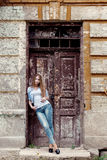 有红色头发的美丽的年轻甜女孩在站立在老城市附近的门的牛仔裤 库存照片