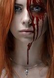 有红色头发的,血淋淋的面孔女孩 库存图片