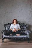 有红色头发的年轻人孕妇坐在巴洛克式的样式的一个灰色沙发 她穿一件白色衬衣的` s,可看见 免版税库存图片