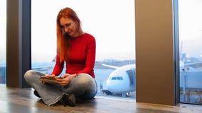 有红色头发的年轻可爱的妇女和玻璃在窗口附近使用小配件在机场 免版税库存图片