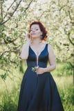 有红色头发的年轻美丽的妇女在摆在一个开花的庭院里的一件蓝色礼服 库存图片