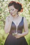 有红色头发的年轻美丽的妇女在摆在一个开花的庭院里的一件蓝色礼服 库存照片