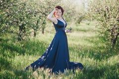 有红色头发的年轻美丽的妇女在摆在一个开花的庭院里的一件蓝色礼服 免版税图库摄影