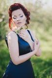 有红色头发的年轻美丽的妇女在摆在一个开花的庭院里的一件蓝色礼服 图库摄影