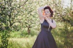 有红色头发的年轻美丽的妇女在摆在一个开花的庭院里的一件蓝色礼服 免版税库存照片